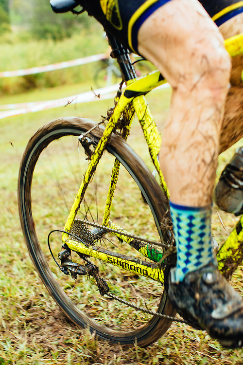 Rear wheel spin going up a wet and grassy hill during a rainy cyclocross event in Samford.