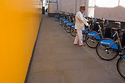 An elderly man considers hiring a Boris Bike from a station of sponsored wheels in central London.