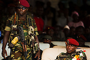 """A soldier stands guard by Guinea's president Captain Moussa Dadis Camara (right) during an official visit at the Kofi Annan private university in Conakry, Guinea on Thursday March 5, 2009. Camara, who took power after a coup in December 2008, was visiting the university to """"meet the youth"""", as part of his efforts to solidify his support from Guinea's population.(Olivier Asselin for the New York Times)"""