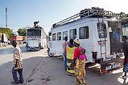 Bij de splitsing van twee snelwegen in Dakar is het een drukte van belang met verkeer en bussen. Er wordt ook druk gehandeld.