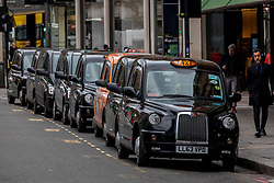 © Licensed to London News Pictures. 13/03/2020. London, UK. Taxis in Knightsbridge next to Harrods. Knightsbridge appears very quiet this morning as Prime Minister Boris Johnson warned that anyone with cold like symptoms should self-isolate as the World Health Organization declares that the Coronavirus disease is a Pandemic. Photo credit: Alex Lentati/LNP