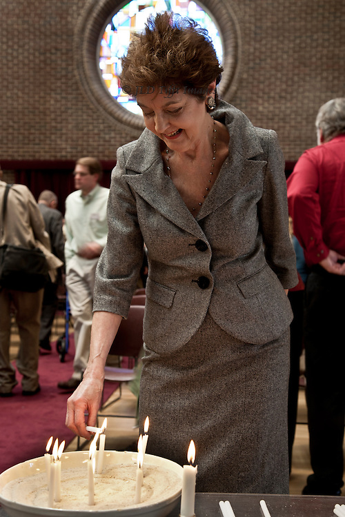 Jeanne Gayler lights a candle after a service.  Circular stained glass window behind her head looks like a halo.