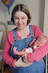 Mother cradling new born baby son in her arms smiling,