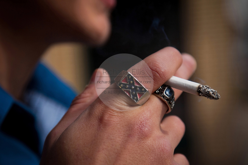 Smoking man with confederate southern emblem ring.