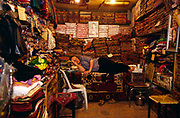 A man asleep inside his shop in the Souk in Aleppo, Syria. The Souk is the longest covered market in the Middle East and parts can be dated to Roman times. The entire covered Souk can be dated from the sixteenth century. Goods ranging from food to jewellery can be purchased here.