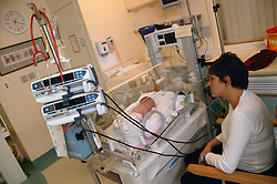 Mother looking at her newborn baby boy in an incubator in the Neonatal unit,