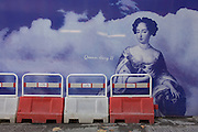 Queen Mary II on a construction hoarding alongside a red standing pedestrian light in central London.