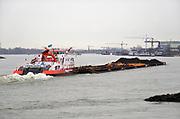 Nederland, Millingen, 6-2-2019 Een binnenvaartschip, duwboot veerhaven met zes bakken met kolen, vaart over de Rijn richting Duitsland .. Verderop ligt scheepswerf voorheen bodewes, nu in handen van Gelria. zesbaks duwvaart combinatie .Foto: Flip Franssen
