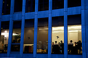 A meeting takes place at an office building in London. Businessmen in discussion illuminated at night.