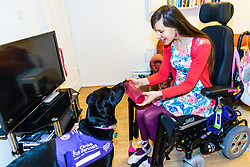 Ethan delivers Sally's water bottle to her after fetching it from the fridge. Illnesses in her teens has left Sally Whitney from Brighton, who suffers from seizures, in a wheelchair and dependent on her assistance dog Ethan. The highly trained black Labrador can get help when she needs it , can fetch and put things away for her, and can even pay for shopping with contactless payment cards. Brighton, March 02 2019.