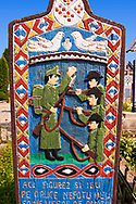 Tombstone of a soldier, The  Merry Cemetery ( Cimitirul Vesel ),  Săpânţa, Maramares, Northern Transylvania, Romania.  The naive folk art style of the tombstones created by woodcarver  Stan Ioan Pătraş (1909 - 1977) who created in his lifetime over 700 colourfully painted wooden tombstones with small relief portrait carvings of the deceased or with scenes depicting them at work or play or surprisingly showing the violent accident that killed them. Each tombstone has an inscription about the person, sometimes a light hearted  limerick in Romanian. .<br /> <br /> Visit our ROMANIA HISTORIC PLACXES PHOTO COLLECTIONS for more photos to download or buy as wall art prints https://funkystock.photoshelter.com/gallery-collection/Pictures-Images-of-Romania-Photos-of-Romanian-Historic-Landmark-Sites/C00001TITiQwAdS8