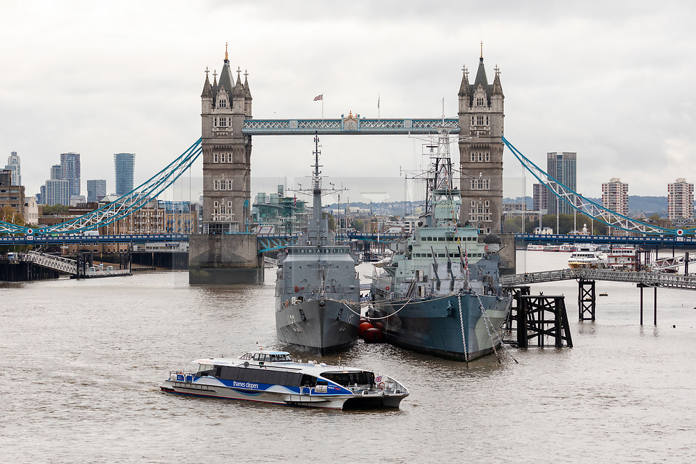 © Licensed to London News Pictures. 16/10/2019. London, UK. A Thames Clipper commuter boat passes Brazilian naval warship, NE Brasil moored next to HMS Belfast in front of Tower Bridge on the River Thames during a London visit. NE Brasil arrived yesterday and will stay until 20th October. Environmental campaign groups are challenging the increasing numbers of large warships, cruise ships and super yachts visiting the capital because of the pollution they create. Photo credit: Vickie Flores/LNP