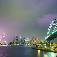 Australia, NSW, Sydney, Lightning strikes above city skyline and Harbour Bridge during summer thunderstorm
