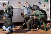 03 MARCH 2003 - PHOENIX, ARIZONA:  Immigration and Customs Enforcement (ICE) officers search undocumented immigrants discovered in a drop house in Phoenix, AZ, before putting them on buses and taking them into ICE detention in Phoenix. Phoenix police and fire departments responded to reports of a migrant drop house in south central Phoenix and found more than 70 undocumented immigrants in the home. The immigrants were turned over to Immigration and Customs Enforcement (ICE) for processing and eventual removal from the US.      PHOTO BY JACK KURTZ