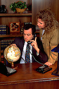 Argentinean businessman age 33 on phone in office with partner age 32.  St Paul Minnesota USA