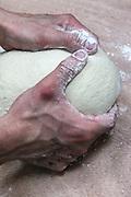 Baker kneads bread dough in a bakery