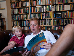 Father reading book to young son in bookshop