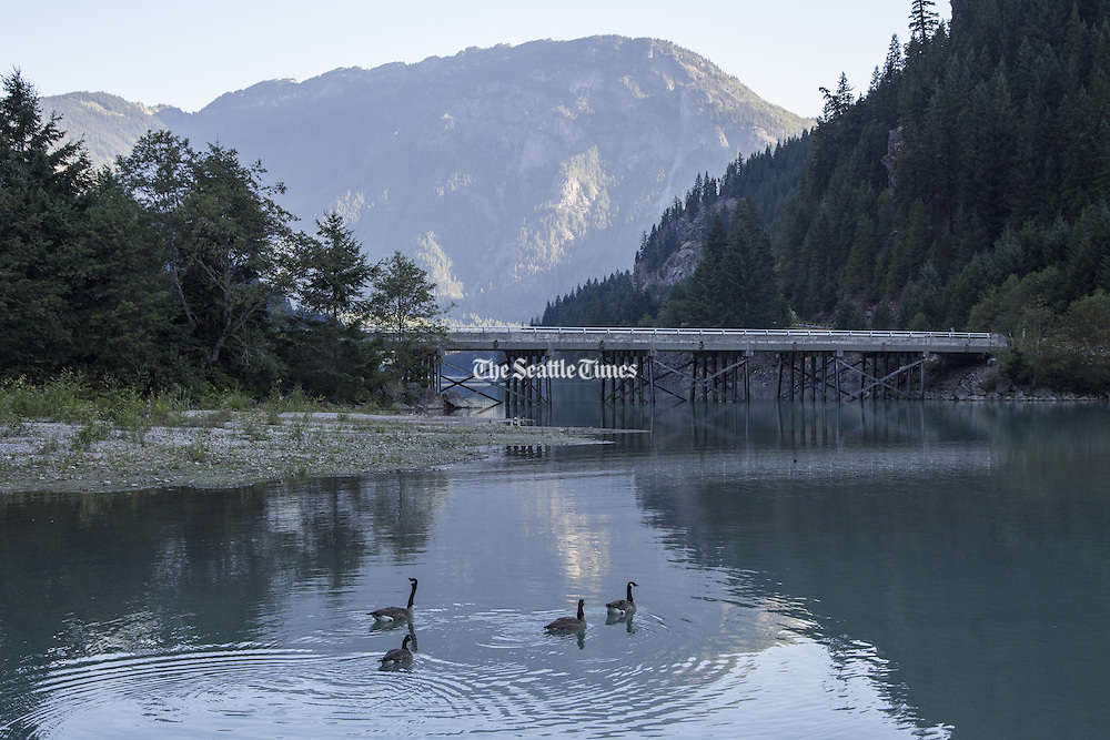 Sunrise on Diablo Lake with Highway 20 in the backround.  In the far backround is Sourdough Mountain. (Steve Ringman / The Seattle Times)