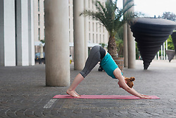 Young woman doing downward facing dog pose on exercise mat in urban city, Freiburg im Breisgau, Baden-Wuerttemberg, Germany