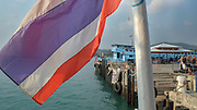Thai flag over the passengers at a port in Ko Pha-ngan, Thailand