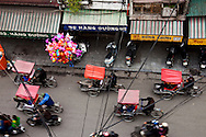 Cyclos crowd the streets of Hanoi during Tet, the Lunar New Year celebration. Families often dress up and take a spin around the city during Tet. Two boats await their time to bring their yellow flowers to the Phong Dien market in Can Tho. Prior to Tet, the Lunar New Year celebration, the markets are flooded with flowers. The flowers are purchased for homes and kept for good luck. Robert Dodge, a Washington DC photographer and writer, has been working on his Vietnam 40 Years Later project since 2005. The project has taken him throughout Vietnam, including Hanoi, Ho Chi Minh City (Saigon), Nha Trang, Mue Nie, Phan Thiet, the Mekong, Sapa, Ninh Binh and the Perfume Pagoda. His images capture scenes and people from women in conical hats planting rice along the Red River in the north to men and women working in the floating markets on the Mekong River and its tributaries. Robert's project also captures the traditions of ancient Asia in the rural markets, Buddhist Monasteries and the celebrations around Tet, the Lunar New Year. Also to be found are images of the emerging modern Vietnam, such as young people eating and drinking and embracing the fashions and music of the West. His book. Vietnam 40 Years Later, was published March 2014 by Damiani Editore of Italy.