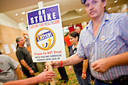 Nov. 11, 2009 -- PHOENIX, AZ: JESSE LADD, an employee of a Frys' grocery store in Mesa, AZ, accepts a picket sign during a meeting of members of the UFCW at the Airport Marriott Hotel in Phoenix. The United Food and Commercial Workers Union (UFCW) Local 99 has about 25,000 members in Arizona: 15,000 in Fry's grocery stores and Fry's Marketplace, 9,500 in Safeway stores and 400 in Smith's grocery stores. The union voted down the last proposal from the stores and has announced plans to go on strike at 6PM on Friday, Nov. 13. The meeting Wednesday is the last one before the strike.   Photo by Jack Kurtz