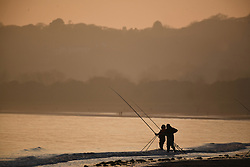 © Licensed to London News Pictures. 29/11/2020. Swansea, UK. Fisherman are pictured on the seafront  at Swansea Bay at the end of beautiful day in Wales and across the UK. Photo credit: Robert Melen/LNP