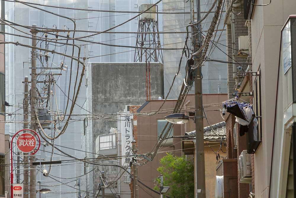 Telephone and electrical wires form a messy tangle above a street in Tokyo, Japan.Friday November 4th 2016
