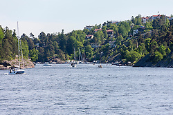 Sailboats in sea with town in the background, Velamsund,  Stockholm, Sweden