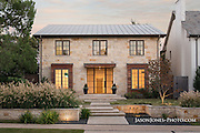 Elegant traditional home, with landscaping, stone work, tiered front yard and metal roof