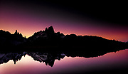 Silhouette of Patagonian mountains, reflection in small lake under Cerro Torre & Monte FitzRoy, Parque Nacional los Glaciares, Patagonia, Argentina.