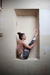 Mid adult woman practicing big toe pose in alcove, Munich, Bavaria, Germany