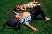 Two 1990s office workers sunbathe on grass during their lunchtime, on the grass in the City of London aka The Square Mile, the capitals financial centre, on 20th June 1992, in London, England.