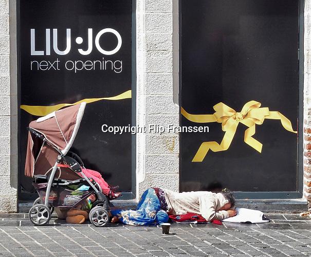 Frankrijk, Lille, 18-8-2013 Het kledingmerk Liu Jo opent binnenkort een nieuwe winkel in deze stad. Een Roma vrouw ligt op straat voor het pand te slapen en bedelen met haar kinderen. Lille ligt in een sterk de verarmde regio noordwest. Het is de hoofdstad van Frans Vlaanderen, van de regio Nord Pas de Calais en van het Noorder departement. Foto: Flip Franssen