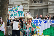 On the day that the new Conservative Party leader Theresa May MP became Prime Minister of the UK, protesters humorously dressed up in face masks and singing amusing political songs mocking the PM outside Downing Street on 13th July 2016 in London, United Kingdom. The leader of the protest dressed up as a joke Theresa May with blonde wig, crudely put on make up, see through plastic dress and wearing pearls, delighted passers by.