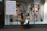 Two Asian girls stand outside the Oxford Street branch of Womens' fashion shop Topshop.