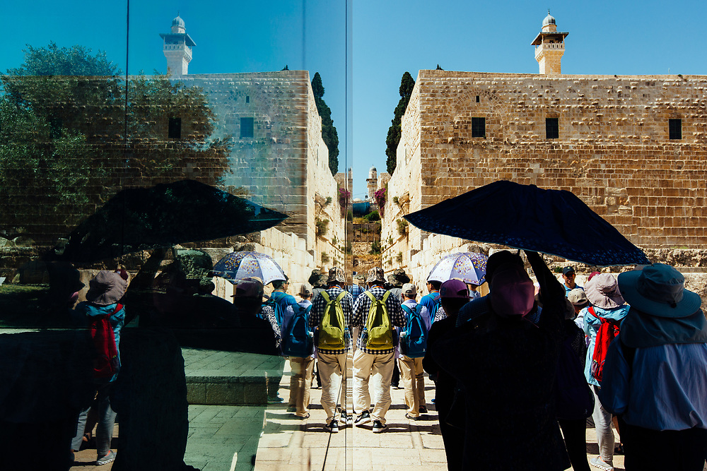Tourists are reflected in the glass facade of the Davidson Center, at the Jerusalem Archaeological Park, in the Old City of Jerusalem