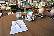 Nederland, Hilversum, 7-8-2020  Bij een cafe in de stad heeft men al formulieren waar bezoekers hun gegevens moeten invullen vanwege een eventueel contactonderzoek bij geconstateerde corona . Gisteren is op een persconferentie bekend gemaakt dat dit een van de aanvullende maatregelen, coronamaatregelen is om een tweede golf en mogelijke sluiting van de horeca te voorkomen .Foto: ANP/ Hollandse Hoogte/ Flip Franssen