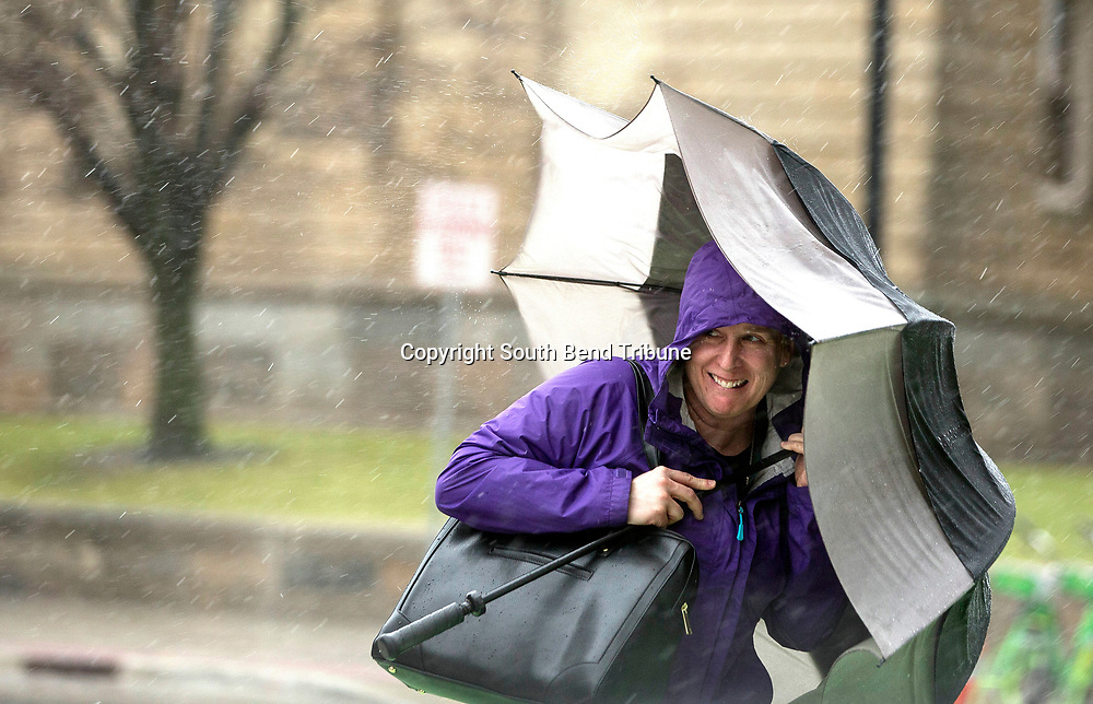 A woman tries to shield herself from heavy rain and strong winds on Tuesday, Feb. 20, 2018, in South Bend. Tribune Photo/SANTIAGO FLORES