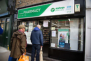 Daily life continues but not as as normal with some rules and restrictions in Hackney on 21st March 2020 in London, United Kingdom. Broadway market on a Saturday morning. Cusomers wait outside a pharmacy which has limited the number who can enter at one time.