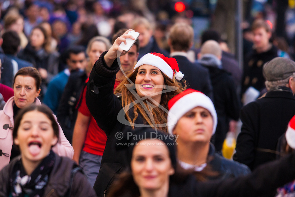 """London, December 23rd 2014. Dubbed by retailers as the """"Golden Hour"""" thousands of shoppers use their lunch hour to do some last minute Christmas shopping in London's West End. PICTURED: A woman takes a selfie as she and thousands of others make their way along Oxford Street."""