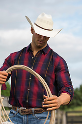 sexy young cowboy on a ranch wearing a flannel shirt and holding a lasso