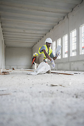 Construction worker using digital tablet at building site, Munich, Bavaria, Germany