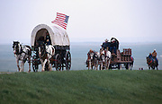 Covered wagons and horseback riders on the modern South Dakota prairie outside Rapid City, South Dakota.