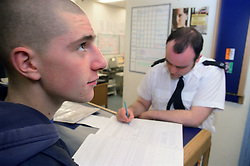 Policeman interviewing teenage young offender in police station,