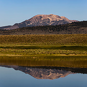 The Sherwin Mountains and Mammoth Mountain glow in the warm reflection of a small lake.