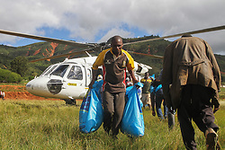 March 22, 2019 - Chimanimani, Zimbabwe - Residents carry food and aid from a helicopter to the survivors. Five days after tropical cyclone Idai cut a swathe through Mozambique, Zimbabwe and Malawi, the confirmed death toll stood at more than 300 and hundreds of thousands of lives were at risk, officials said. (Credit Image: © Tafadzwa Ufumeli/ZUMA Wire)