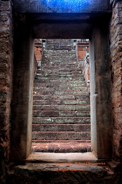 Stairs to Light: Seen from within the darkened ruins at Angkor Wat Cambodia, a set of steep stairs climb towards the light of day.