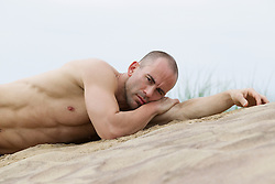 man without a shirt resting on a sand dune