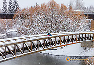 Couple on Footbridge across the Whitefish River on snowy day in Whitefish, Montana, USA